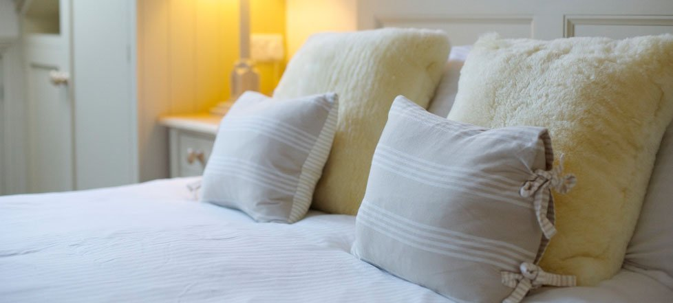 Large fluffy pillows and cushions on a bed at The Rose And Crown