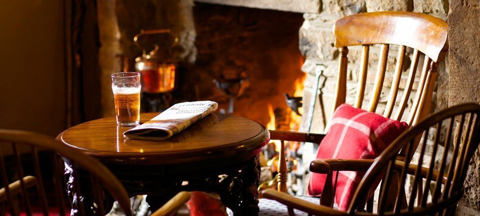 A pint of beer and a newspaper on a table positioned in front of a roaring fire
