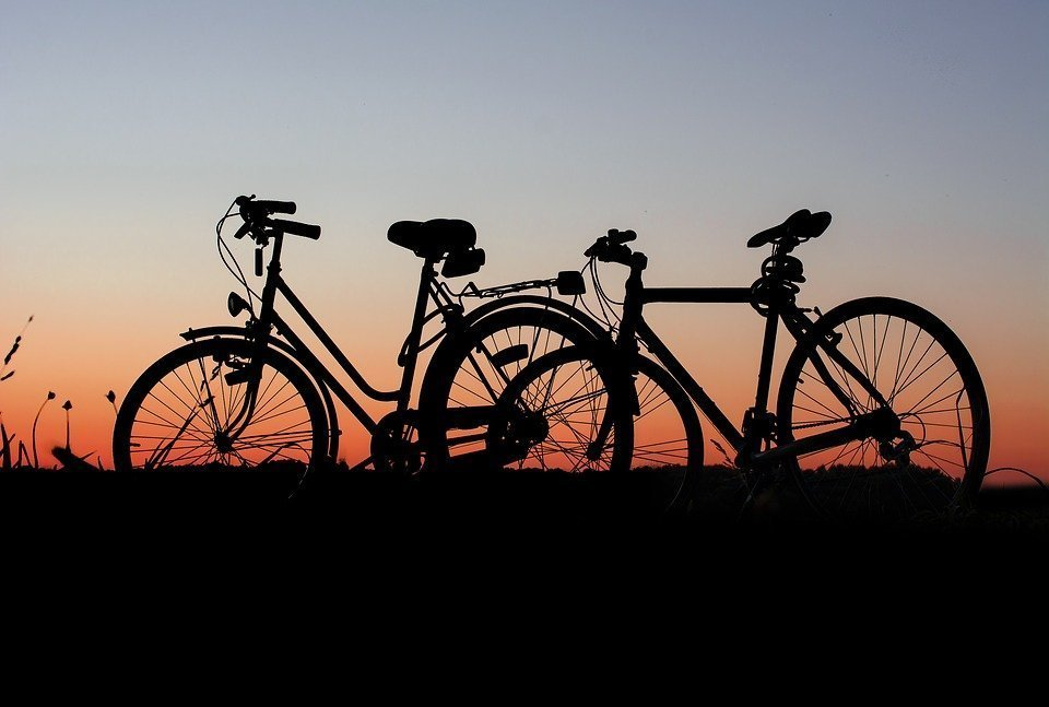 A silhouette of two bicyles